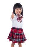 Pequeña muchacha china asiática feliz del estudiante que muestra los pulgares para arriba Imagen de archivo libre de regalías