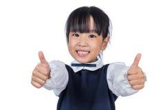 Pequeña muchacha china asiática feliz del estudiante que muestra los pulgares para arriba Fotos de archivo libres de regalías