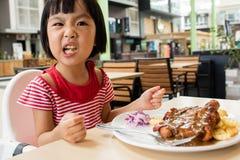 Pequeña muchacha china asiática que come la comida occidental Fotos de archivo libres de regalías