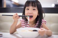 Pequeña muchacha china asiática que come la sopa de tallarines Imagenes de archivo