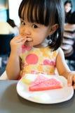 Pequeña muchacha china asiática que come las frutas Fotografía de archivo
