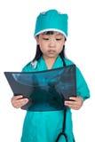 Pequeña muchacha china asiática que juega al doctor con el estetoscopio y el x imagen de archivo