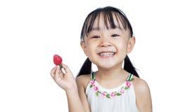 Pequeña muchacha china asiática que sostiene la fresa Imagen de archivo libre de regalías