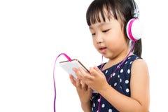 Pequeña muchacha china asiática que usa el teléfono móvil con las auriculares Imagen de archivo