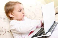 Pequeña muchacha con la computadora portátil Imagen de archivo