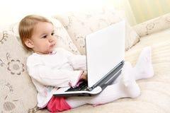 Pequeña muchacha con la computadora portátil Fotos de archivo libres de regalías