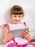 Pequeña muchacha con la tableta Imagen de archivo