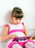 Pequeña muchacha con la tableta Imágenes de archivo libres de regalías