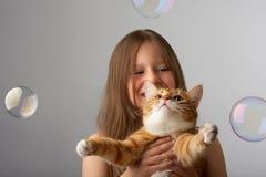 Pequeña muchacha con un gato rojo Foto de archivo