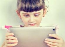 Pequeña muchacha con una tableta Foto de archivo libre de regalías