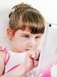 Pequeña muchacha con una tableta Fotografía de archivo libre de regalías
