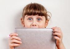 Pequeña muchacha con una tableta Imagenes de archivo