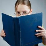 Pequeña muchacha de la pupila con los libros Fotos de archivo libres de regalías
