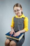 Pequeña muchacha de la pupila con los libros Fotografía de archivo