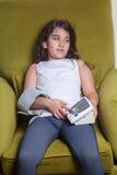 Pequeña muchacha de Oriente Medio que siente malo enfermo y que lleva a cabo el dispositivo digital de la presión arterial Fotografía de archivo
