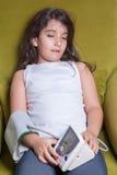 Pequeña muchacha de Oriente Medio que siente malo enfermo y que lleva a cabo el dispositivo digital de la presión arterial Imagen de archivo libre de regalías