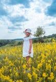 Pequeña muchacha de risa linda que camina en el campo de flores amarillas Fotos de archivo