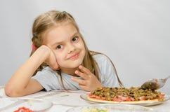 Pequeña muchacha de seis años que se sienta en la tabla que espera alrededor preparando la pizza Imágenes de archivo libres de regalías