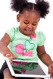 Pequeña muchacha del afroamericano que usa una PC de la tablilla Fotos de archivo libres de regalías