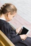 Pequeña muchacha del alumno con la tableta que se sienta en banco Imagen de archivo libre de regalías