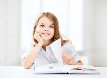 Pequeña muchacha del estudiante que estudia en la escuela Imagen de archivo libre de regalías