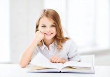 Pequeña muchacha del estudiante que estudia en la escuela Imágenes de archivo libres de regalías