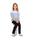 Pequeña muchacha del estudiante que se sienta en la pila de libros Fotografía de archivo