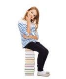 Pequeña muchacha del estudiante que se sienta en la pila de libros Imagen de archivo libre de regalías