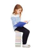 Pequeña muchacha del estudiante que se sienta en la pila de libros Fotos de archivo libres de regalías