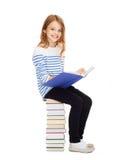 Pequeña muchacha del estudiante que se sienta en la pila de libros Imagenes de archivo