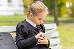 Pequeña muchacha del estudiante que usa la tableta digital Fotos de archivo