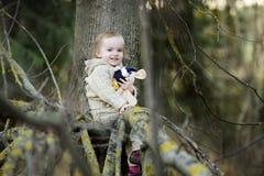 Pequeña muchacha del niño que se sienta en una ramificación de árbol Fotos de archivo libres de regalías