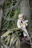 Pequeña muchacha del niño que se sienta en una ramificación de árbol Foto de archivo libre de regalías