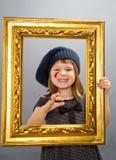 Pequeña muchacha del pintor que mira a través de un marco del vintage Fotos de archivo