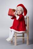 Pequeña muchacha divertida con el regalo de la Navidad Imagen de archivo