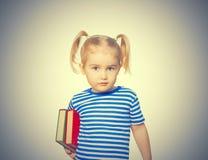 Pequeña muchacha divertida con los libros Imagen de archivo libre de regalías
