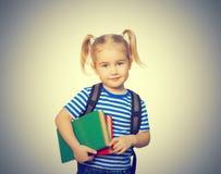 Pequeña muchacha divertida con los libros Fotos de archivo libres de regalías