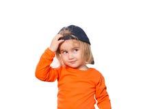 Pequeña muchacha divertida en gorra de béisbol y blusa anaranjada Fotos de archivo libres de regalías