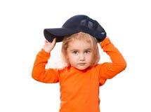 Pequeña muchacha divertida en gorra de béisbol y blusa anaranjada Foto de archivo libre de regalías