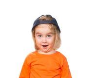 Pequeña muchacha divertida en gorra de béisbol y blusa anaranjada Fotografía de archivo
