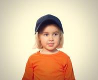 Pequeña muchacha divertida en gorra de béisbol y blusa anaranjada Imagen de archivo libre de regalías