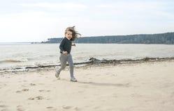 Pequeña muchacha dulce con el pelo largo marrón que corre en la playa en un día nublado Vacaciones por el mar Muchacha linda del  imagenes de archivo