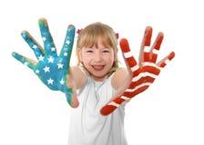 Pequeña muchacha dulce y linda feliz del pelo rubio que muestra las manos pintadas con la bandera de Estados Unidos Foto de archivo libre de regalías