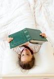 Pequeña muchacha elegante que lee el libro viejo grande en cama Fotos de archivo libres de regalías