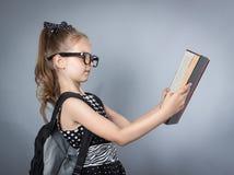 Pequeña muchacha elegante que lee un libro Fotografía de archivo