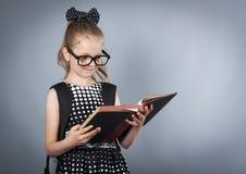 Pequeña muchacha elegante que lee un libro Fotografía de archivo libre de regalías
