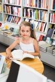 Pequeña muchacha elegante que lee un libro en la biblioteca escolar Fotografía de archivo