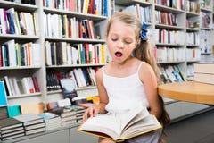 Pequeña muchacha elegante que lee un libro en la biblioteca escolar Fotografía de archivo libre de regalías