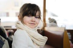 Pequeña muchacha en ropa del invierno en tren del viejo estilo Imágenes de archivo libres de regalías