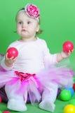 Pequeña muchacha en traje de la rosa en fondo verde Foto de archivo